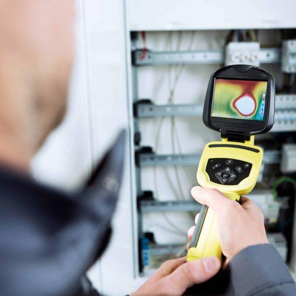 Elektrofachmann vor Schaltkasten mit Wärmebildkamera (1)